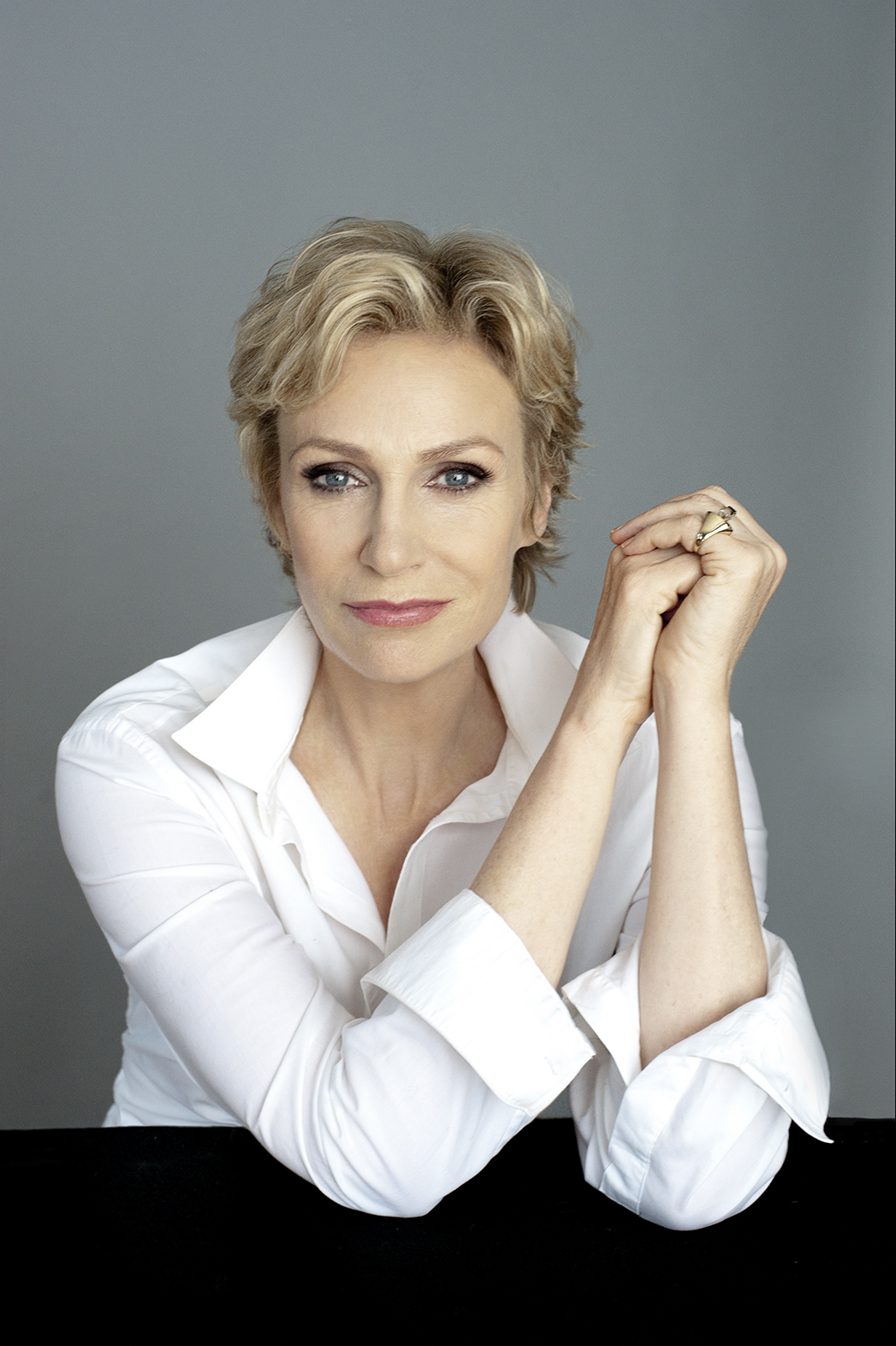 Jane Lynch wears a collared white shirt and poses with her arms folded next to her face