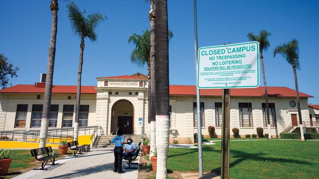 Two security guards at Compton's McKinley Elementary School in April, after Los Angeles Unified schools were shut down because of the COVID-19 pandemic.