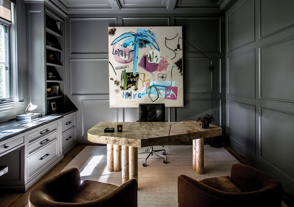 """Office: Farrow & Ball's Down Pipe paint gives Mike Mahan's home office a """"serious and moody"""" feel, says his wife, Brooke. Danielle Siggerud's Mattina table, used as a desk, sits on a rug from Lawrence of La Brea. The two upholstered mohair chairs are vintage Milo Baughman. The artwork is by Ammon Rost. Says Mike, """"We were introduced to Jake through a friend and were immediately drawn to his style."""""""