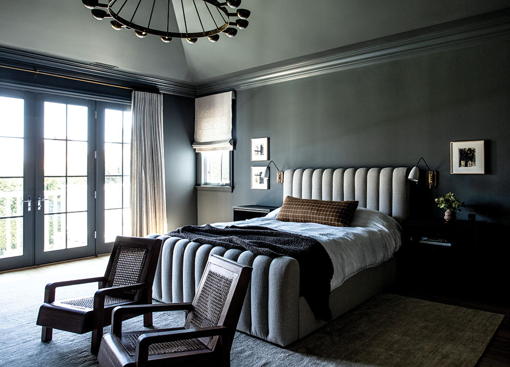 """Bedroom: """"They really wanted it to be comfortable and cozy, but at the same time they wantedto be able to use the spaces and really keep it feeling a little more modern and pared back,"""" says Arnold of the overallaesthetic. Bedroom details include Farrow & Ball's Down Pipe paint, custom bed and nightstands, rug from Woven, vintage chairs from Orange and vintage ceiling fixture from 1st Dibs."""